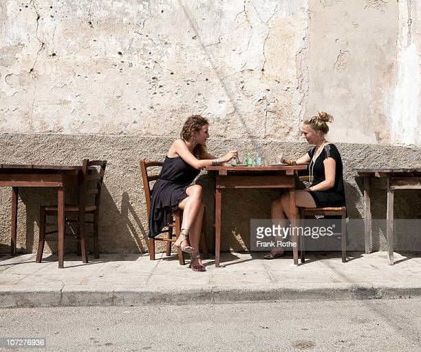 two young woman having a coffee at a street cafe - pavement cafe stock pictures, royalty-free photos & images