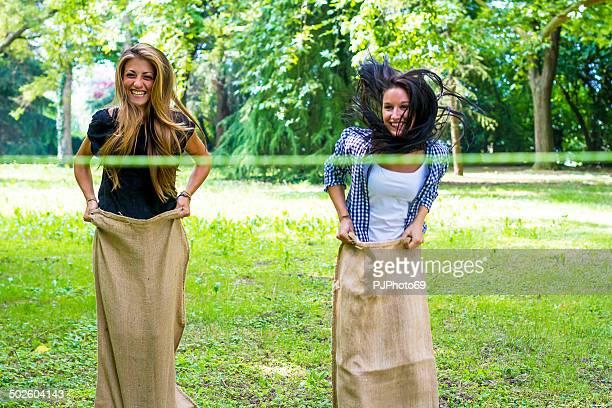 2 つの若い女性をする麻袋競争