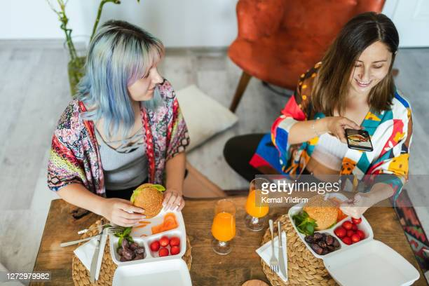 two young woman having vegetarian takeaway meal at home - veggie burger stock pictures, royalty-free photos & images