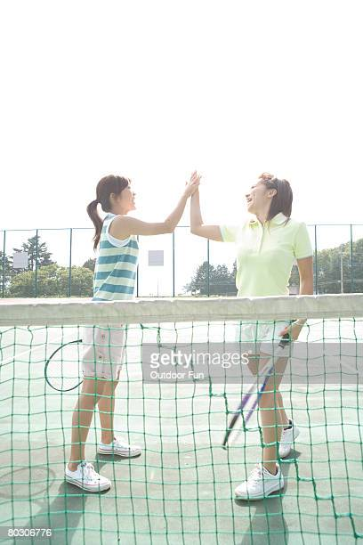 Two young woman high-five in tennis court