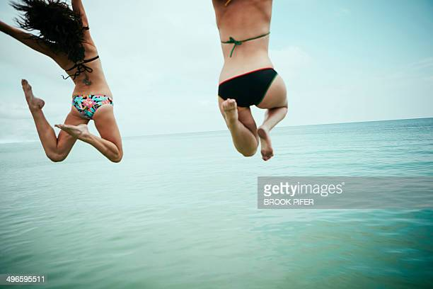 Two young woman jumping into ocean