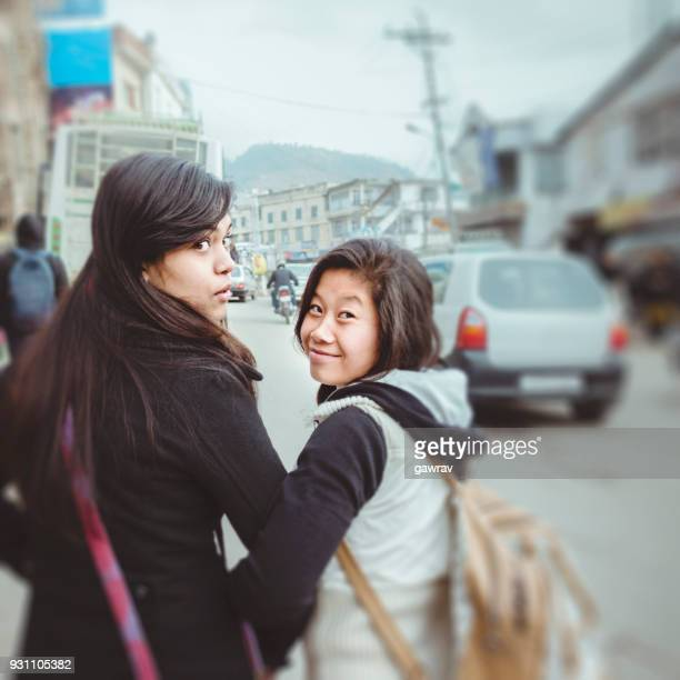 Two young woman Looking back over shoulder while going away.
