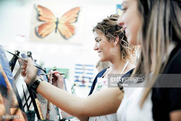 two young woman painting a picture together in a studio - robb reece stock photos and pictures