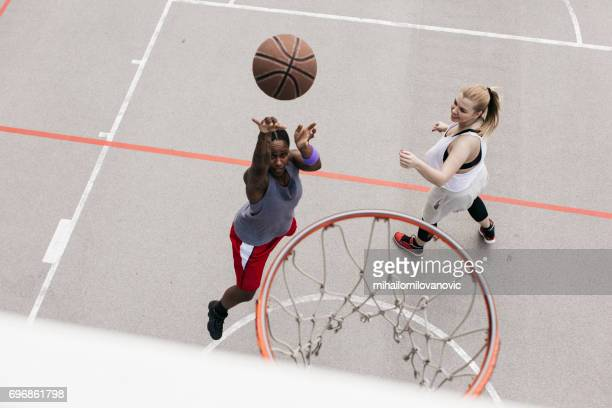 Two young woman playing basketball