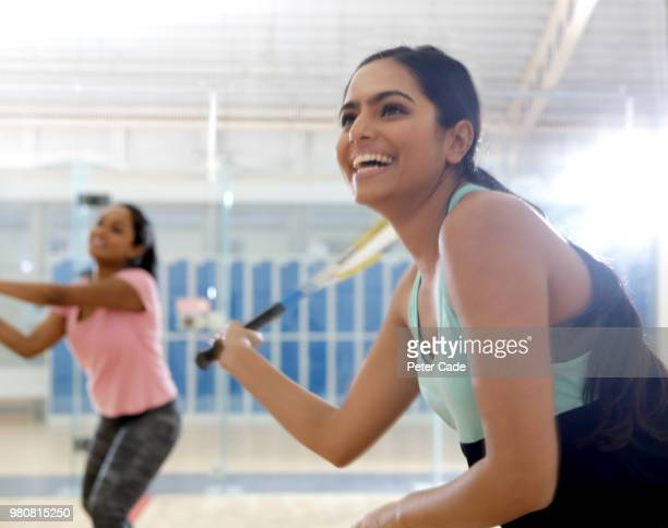 Two young woman playing squash