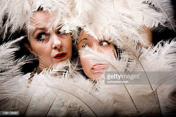 two young woman posing behind feather fans - burlesque stock pictures, royalty-free photos & images