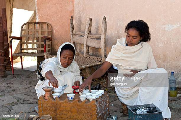 Two young woman preparing a traditional coffee ceremony, Ethiopia