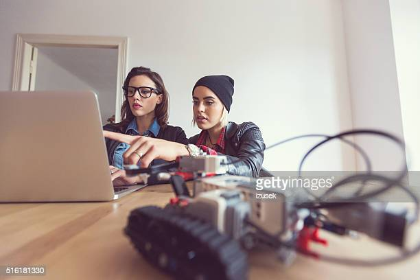two young woman programming a robot - leisure games stock pictures, royalty-free photos & images