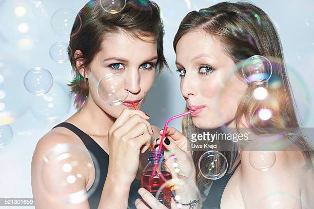 Two young woman sharing drink using straws