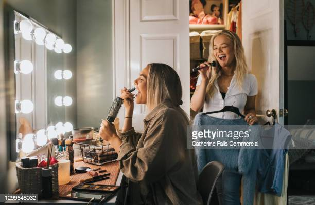 two young woman sing into hairbrushes as they get ready for an event - celebrities stock pictures, royalty-free photos & images