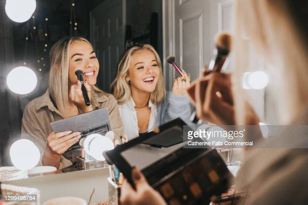 two young woman sit in front of an illuminated mirror and apply make-up - applying stock pictures, royalty-free photos & images