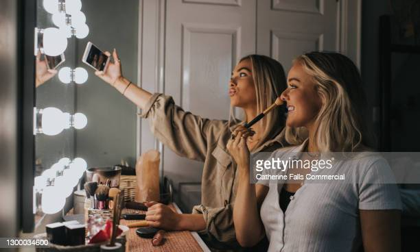 two young woman sit infront of a illuminated mirror and take a selfie - facebook stock pictures, royalty-free photos & images