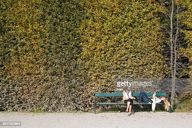 Two Young Woman Sit on a Bench in a Leisure Time in Front of Green and Yellow Leaf Wall