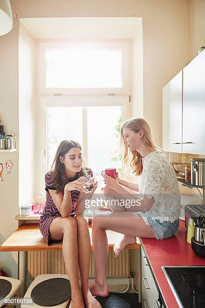 Two young woman sitting on kitchen counter chatting