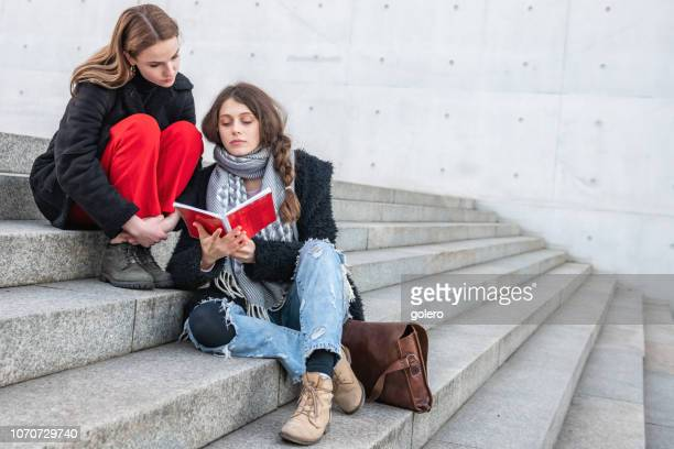 two young woman sitting on stairs outdoors - northern european descent stock pictures, royalty-free photos & images