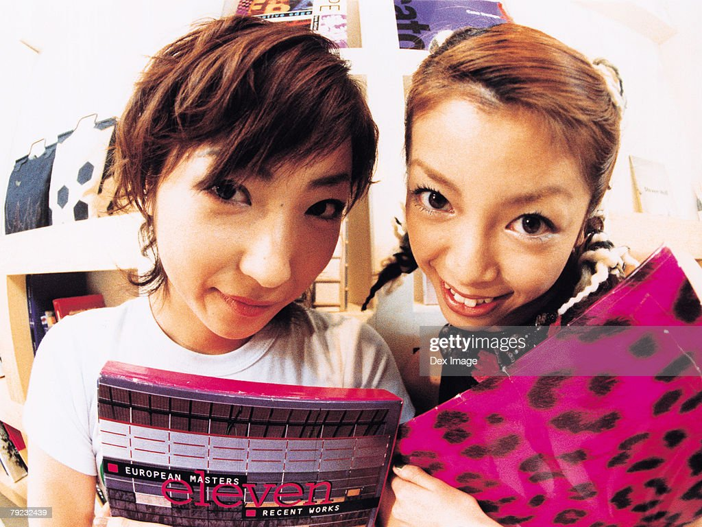 Two young woman smiling, carrying books, close up : Stock Photo