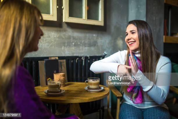 twee jonge vrouwen spreken in gebarentaal - gebaren stockfoto's en -beelden