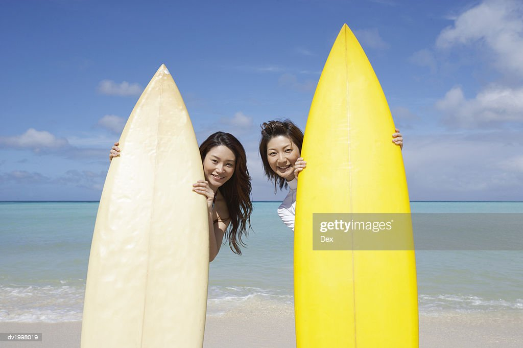 Two Young Woman Stand Behind Surfboards on the Beach, Peeking : Stock Photo