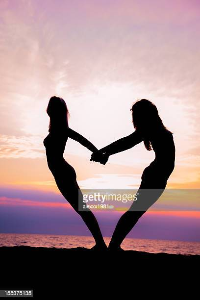 Two young woman standing at sunset beach
