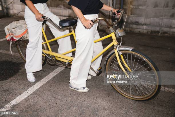two young woman trying to ride a tandem bicycle - tandem bicycle stock pictures, royalty-free photos & images