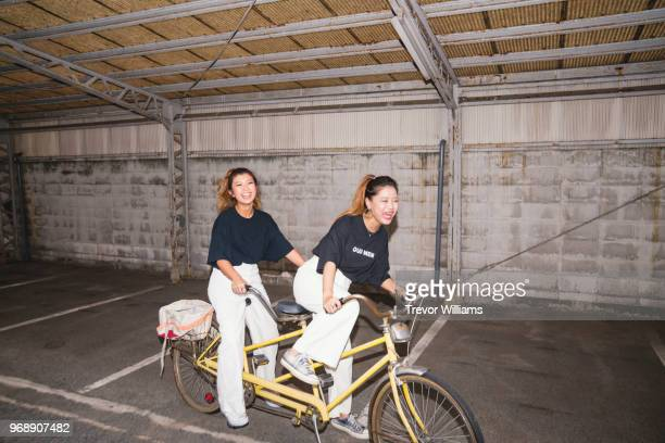 two young woman trying to ride a tandem bicycle - exclusivamente japonés fotografías e imágenes de stock