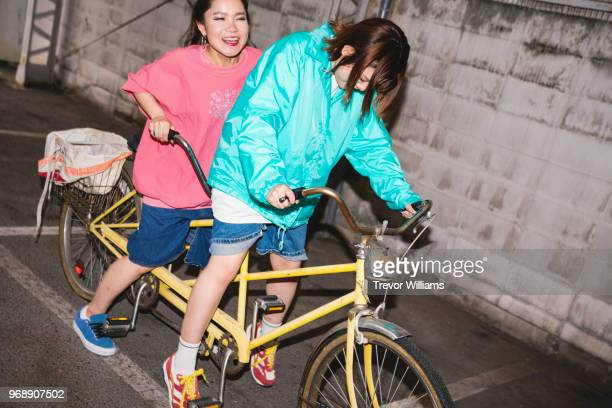 two young woman trying to ride a tandem bicycle - velo humour photos et images de collection