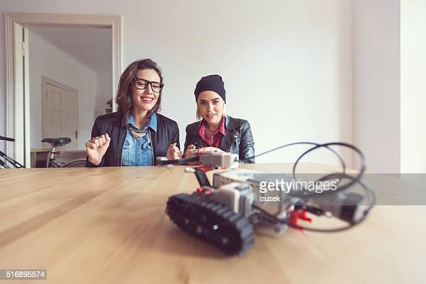Zwei junge Frau mit einem Roboter