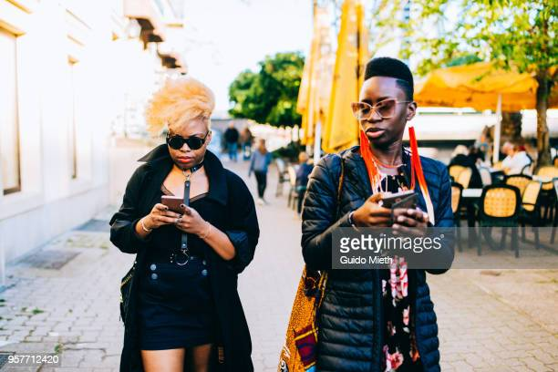 Two young woman using mobile phone in the street.