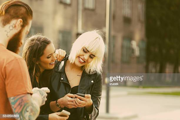 Two young woman using smart phones outdoor