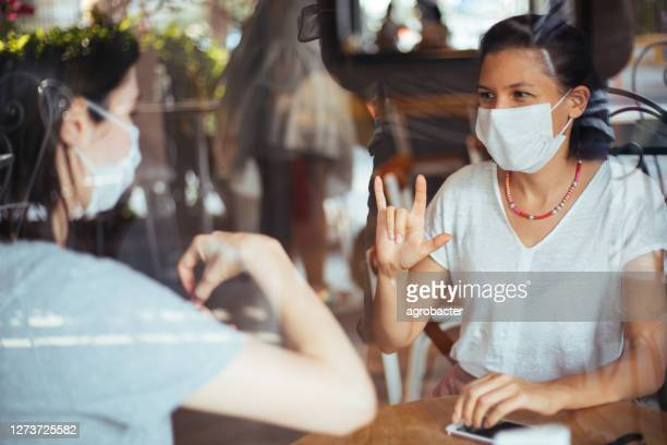 two young woman with mask speak in sign language - persons with disabilities stock pictures, royalty-free photos & images
