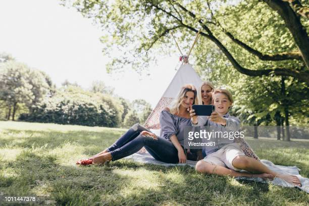 two young women and a boy taking a selfie next to teepee in a park - teepee stock pictures, royalty-free photos & images