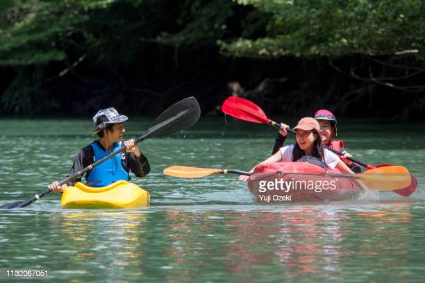 two young women and a man enjoy a kayak with a smile on a sunny lake - カヌー ストックフォトと画像