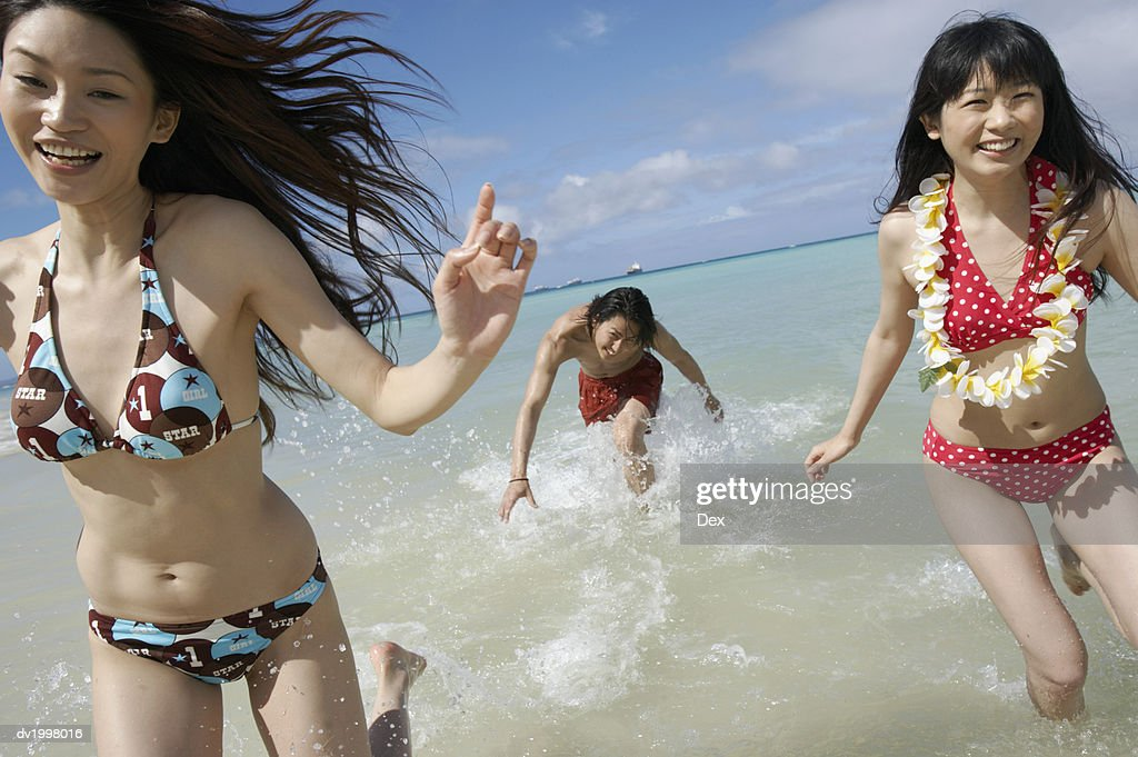 Two Young Women and a Man in Swimwear Run in the Sea, Laughing : Stock Photo