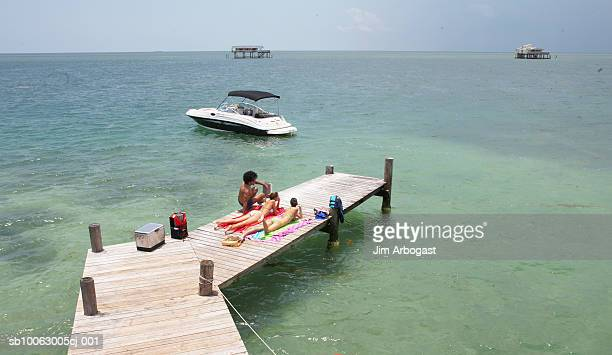 Two young women and man relaxing on jetty, elevated view