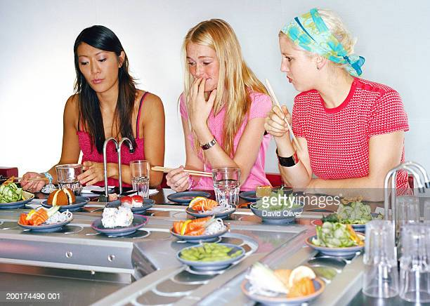 Two young women and teenage girl (13-15) eating at sushi bar
