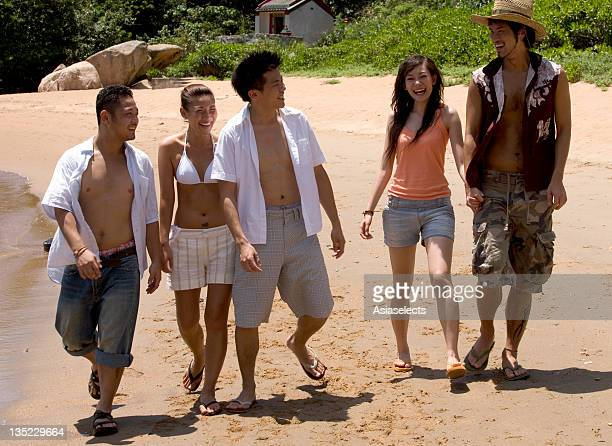 Two young women and three young men walking together on the beach