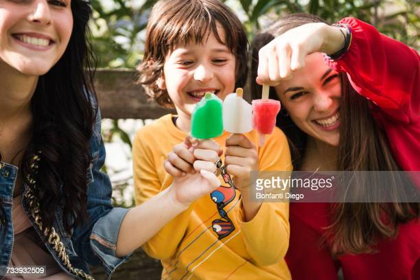 two young women and young boy, sitting on bench, holding ice lollies together to create colours of italian flag - drapeau italien photos et images de collection