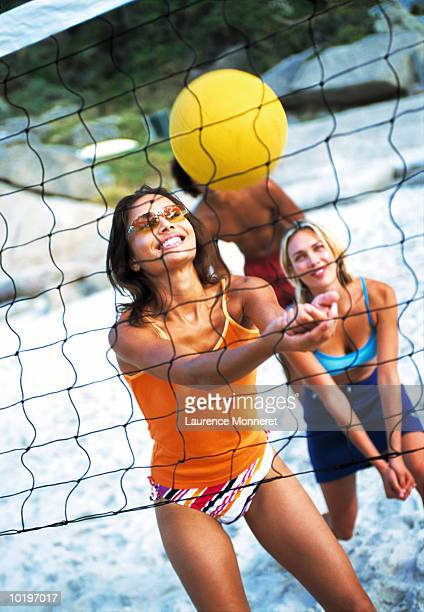 two young women and young man playing volleyball on beach - beach volleyball stock pictures, royalty-free photos & images