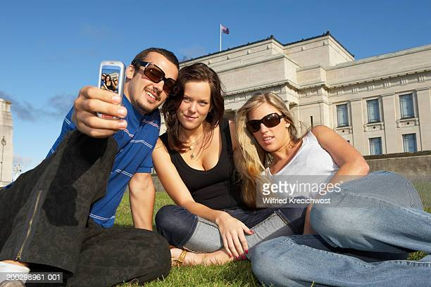 two young women and young man taking photo of themselves, smiling - auckland museum stock photos and pictures