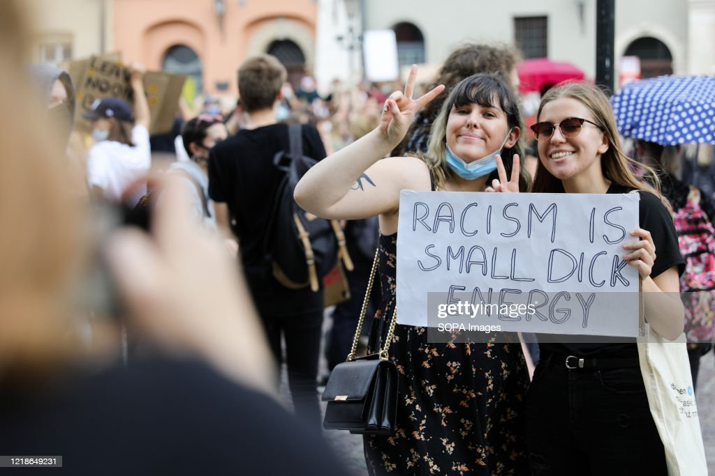 Two young women are seen holding anti racist slogan placards... : News Photo