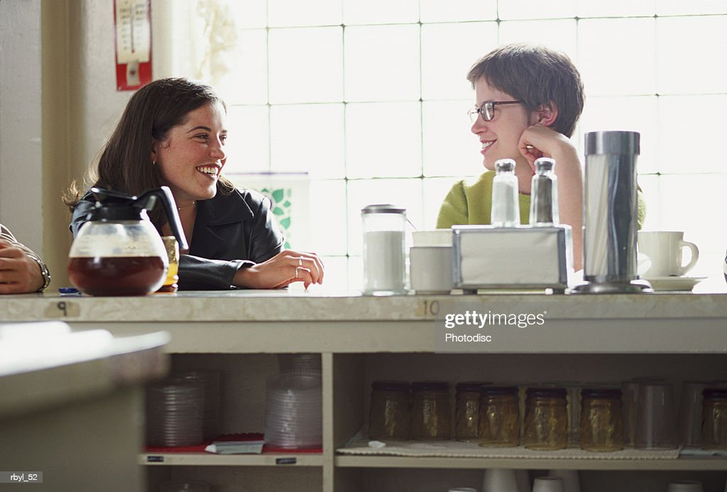 two young women are sitting at the counter of a restauraunt or cafe talking to eachother : Foto de stock