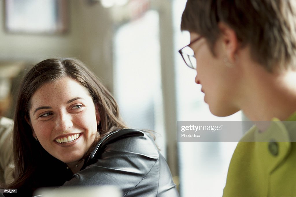 two young women are talking to eachother : Foto de stock