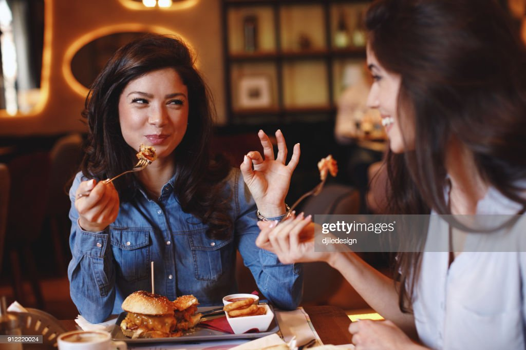 Two young women at a lunch in a restaurant : Stock Photo