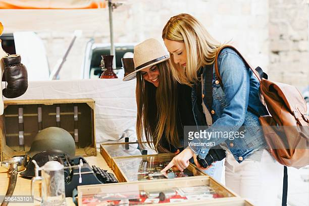 Two young women at a stall on flea market