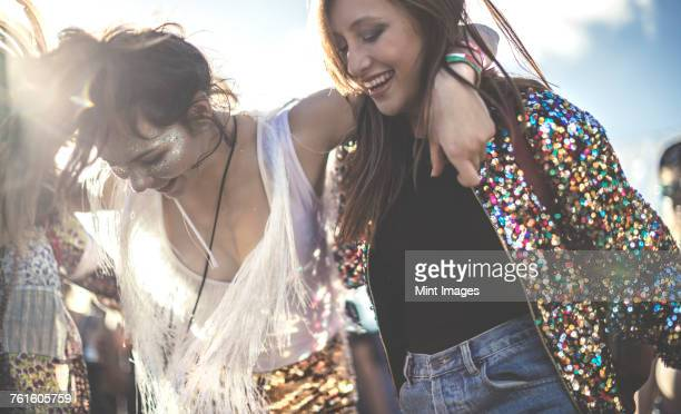 two young women at a summer music festival wearing sequins with painted faces laughing and dancing. - fan enthusiast stock pictures, royalty-free photos & images