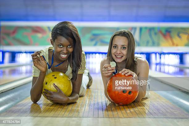 Two young women at bowling holding medals