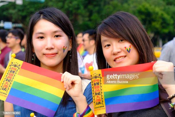 Two young women at the LGBT organized rally in downtown Taipei holding rainbow flags in support to same sex marriage which was legalized in Taiwan in...