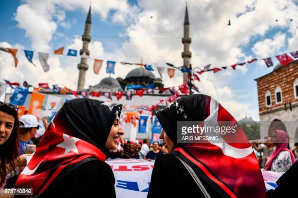 TOPSHOT Two young women attend a presidential campaign happening at a proErdogan supporters' kiosk in Istanbul on June 19 2018 Under Erdogan Turkey...