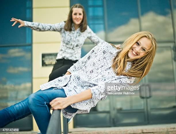 two young women balanced on railings - dreiviertelansicht stock-fotos und bilder