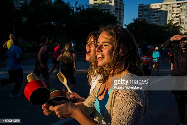 Two young women bang pots and cheer on runners in the Miami Marathon January 25, 2015 in Miami Beach, Florida. More than 20,000 people from 80...
